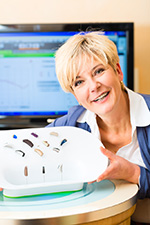 Smiling, friendly Audiology specialist displaying choices in hearing aids.