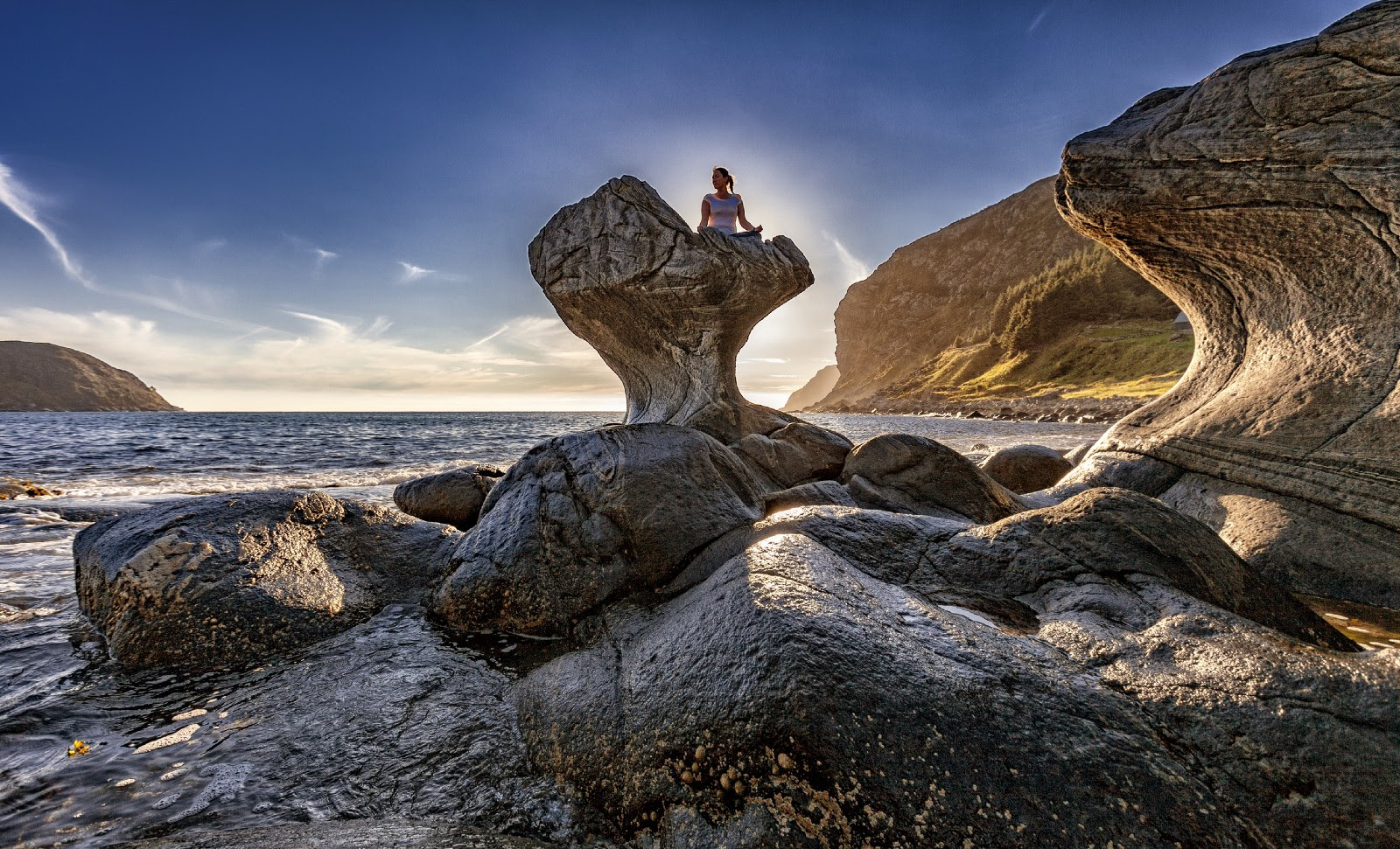 Woman sitting on a rock looking out a beautiful ocean waves and landscapes