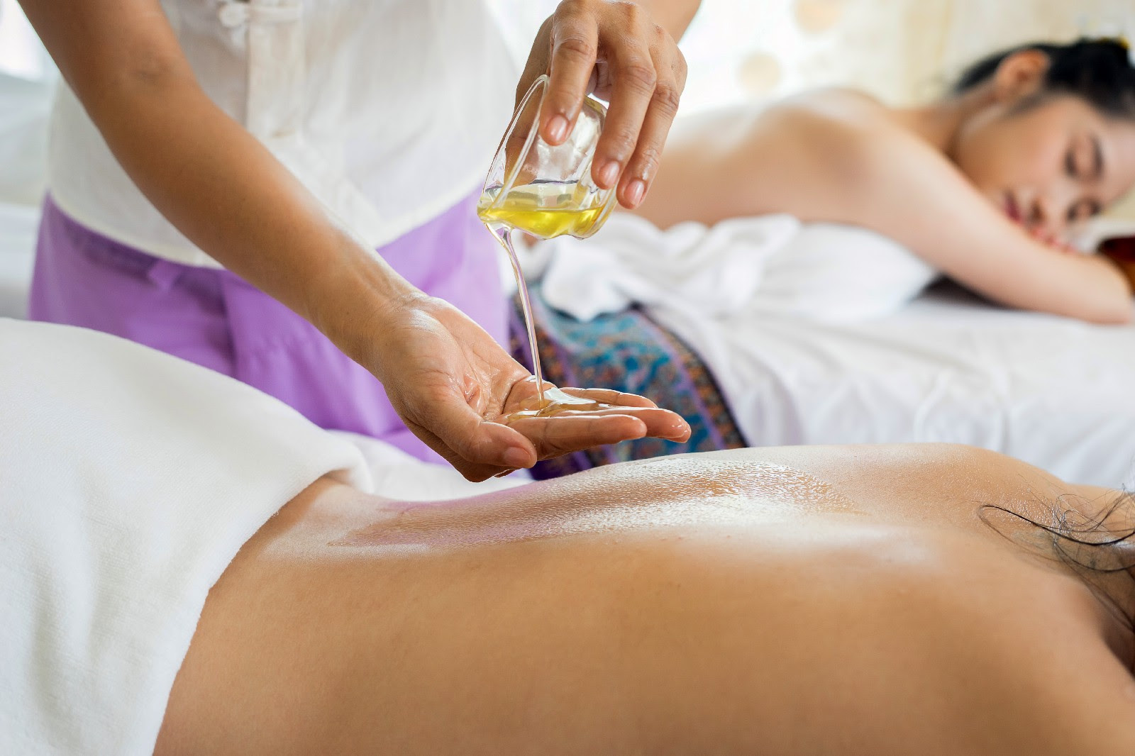 Two women lying face down about to get a massage. A massage therapist pouring oil onto his hand just above the back of one woman.