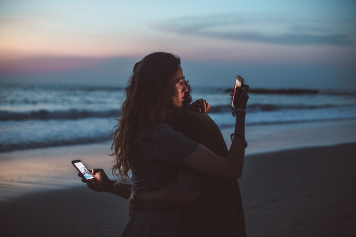 A couple embracing on a beach while looking at their phones