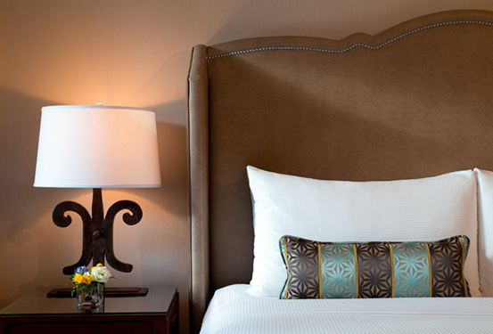 Hotel photography detail shot of bed, nightstand and lamp from The Fairmont Château Lake Louise in Alberta, Canada