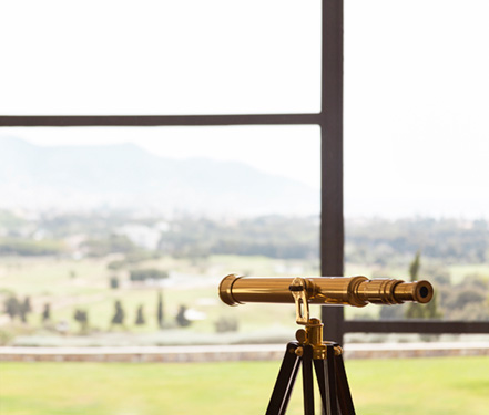 Detail Photography of a gold telescope looking out  a window from Dolce Sitges Hotel in Spain