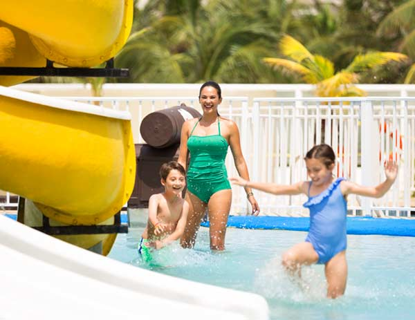 Lifestyle photography of mom and children playing in outdoor swimming pool at Playa Hotels and Resorts' Hyatt Ziva Cancun in Mexico