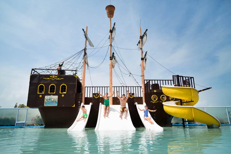 Playa Gran Caribe Cancun lifestyle photography of family sliding down pirate ship water slides into pool