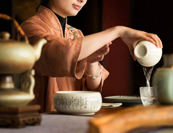 Aspirational photography of woman pouring tea into a cup from Kempinski Hotel Fuzhou in China