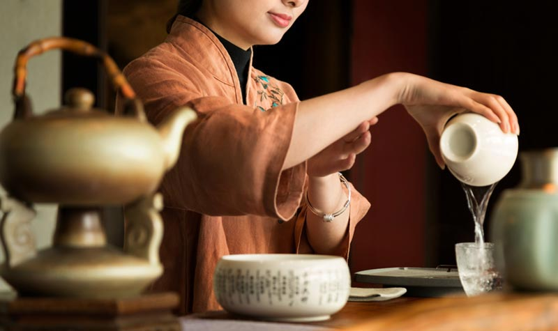 Human Element photography of tea service with model at Kempinski Hotel Fuzhou