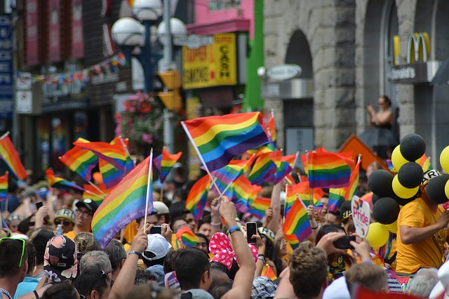 gay pride flags waving in air during a parade