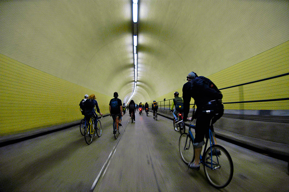 group of people riding their bicycles in a tunnel