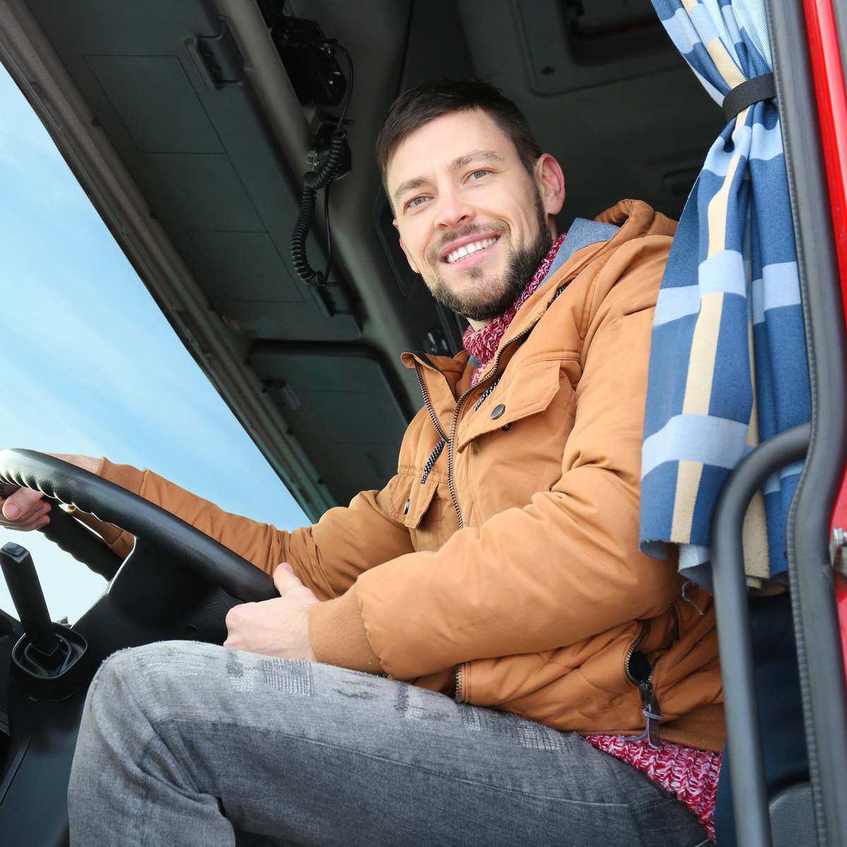Man driving truck while smiling