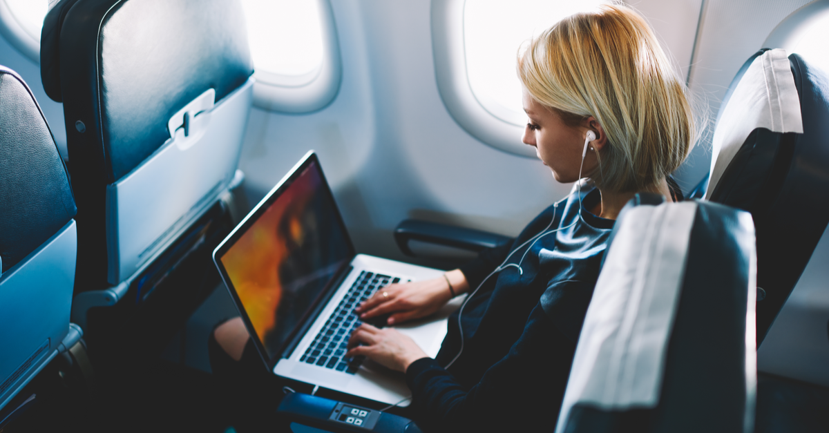 Girl on her laptop while on airplane