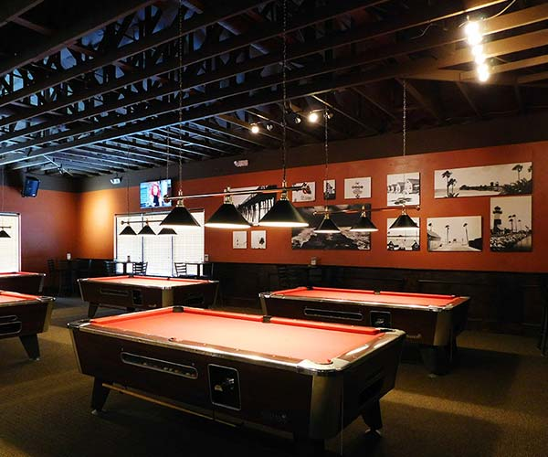 Photo of pool tables at a bar in front of a red wall.