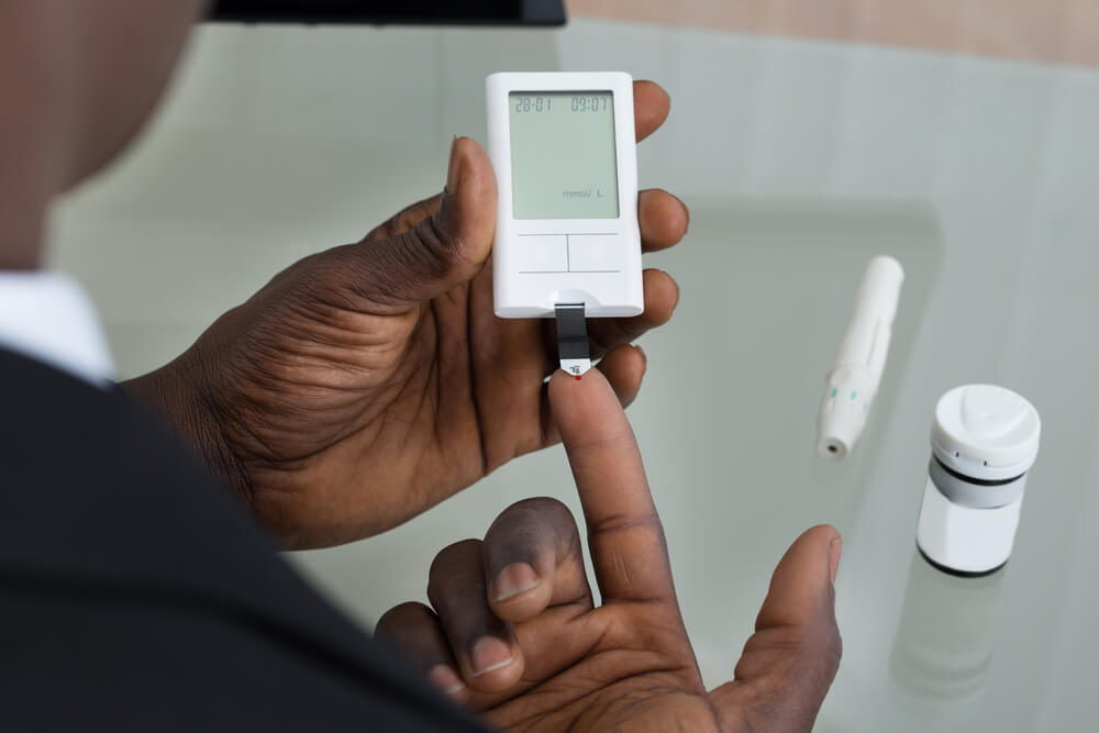 An African American man checking his glucose levels