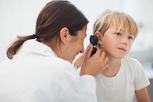 Audiologist examining a child's ear with an otoscope.