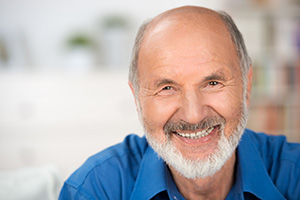 Smiling man who uses modern hearing aid technology to enjoy the world around him.