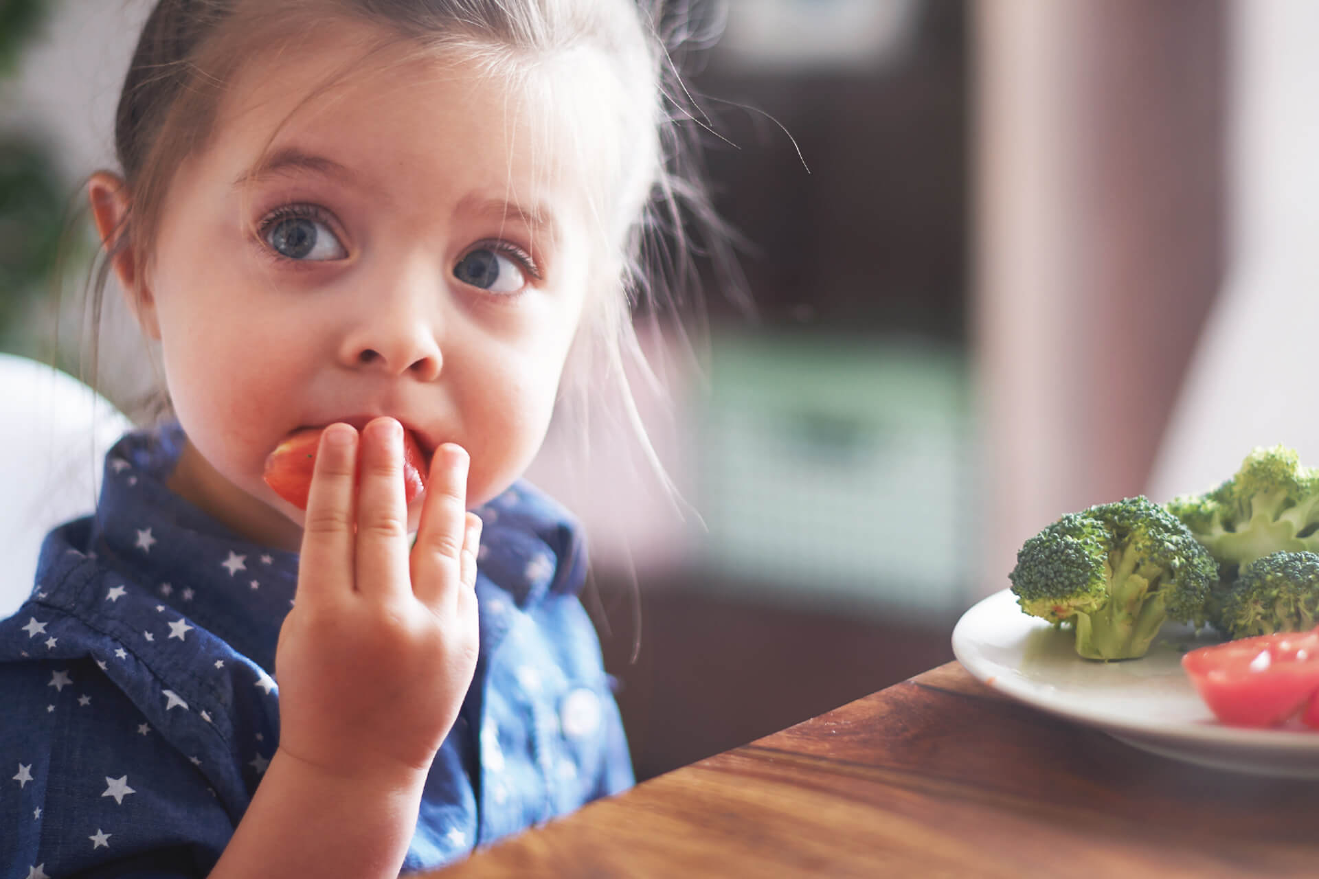 Child at Table Eating Vegetables
