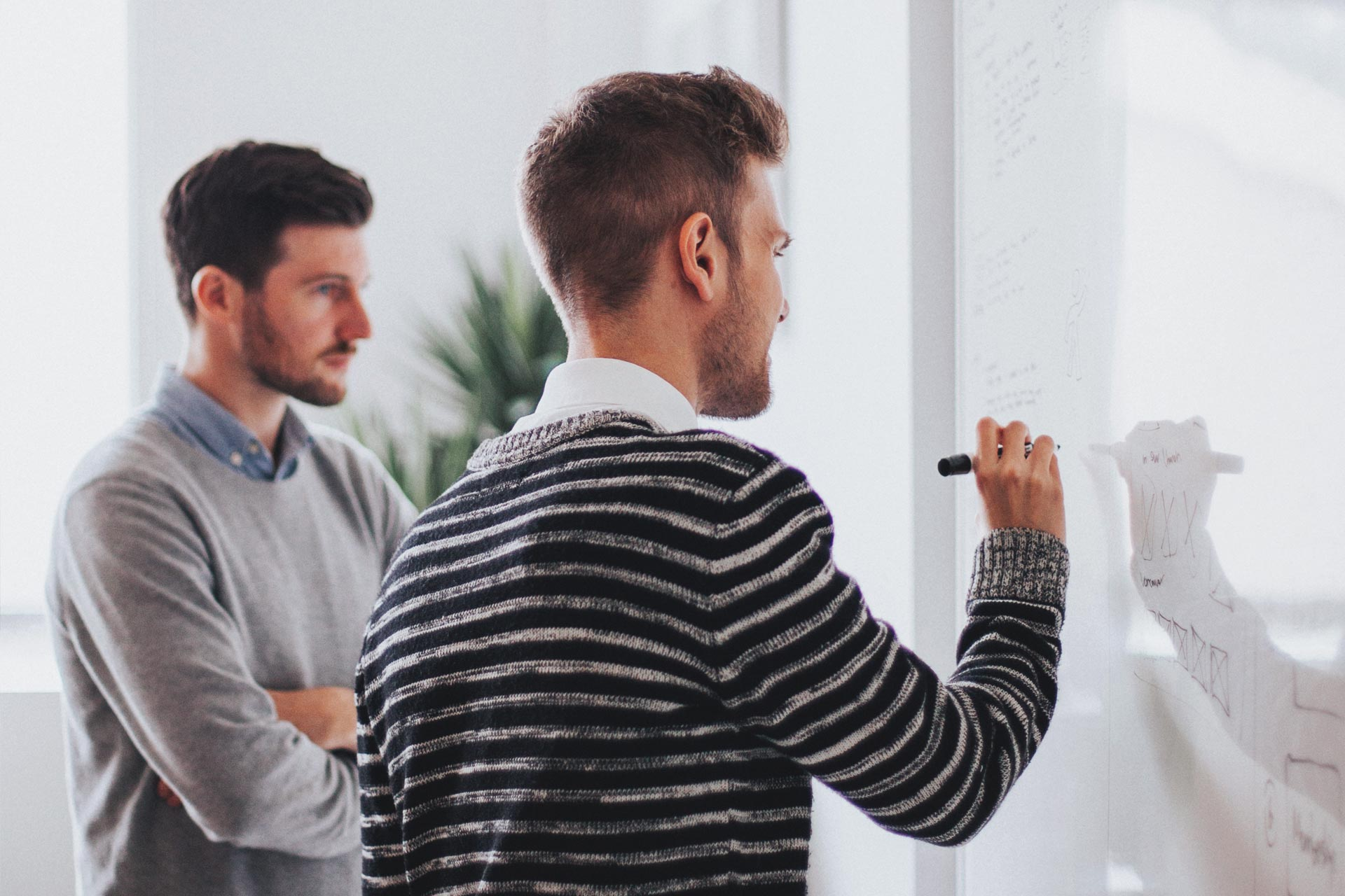 Two designers using a white board