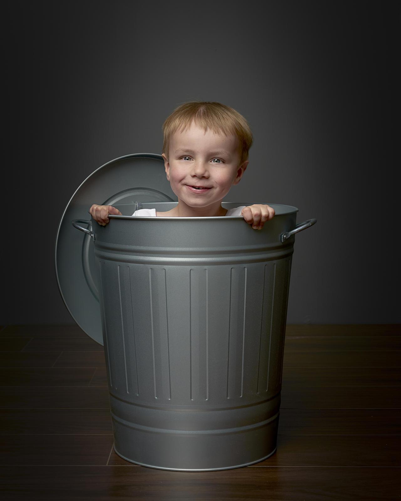 Foto van een gezicht van een jongetje dat uit een blikken ton steekt