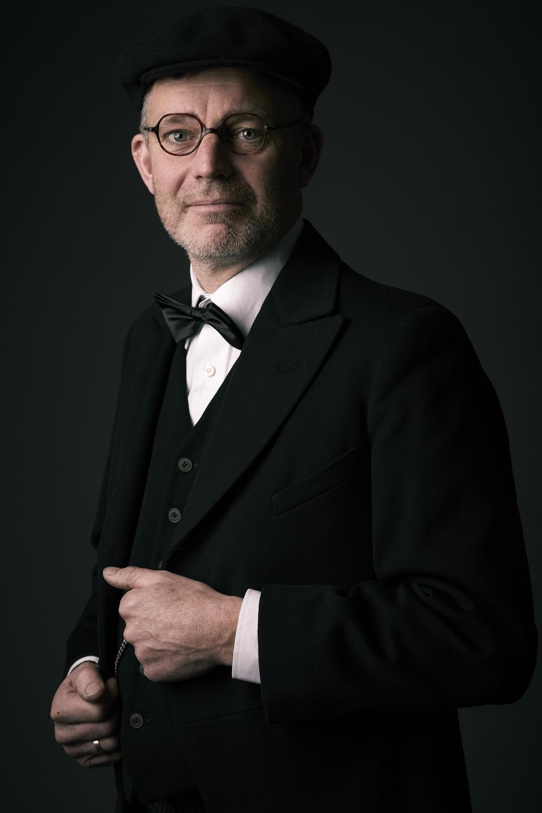 Foto van een man in een net pak die handen aan vest vasthoudt