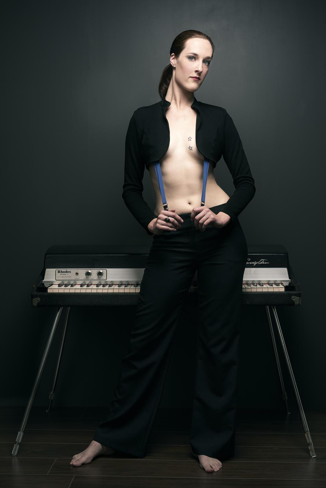 Foto van een vrouw tegen een piano geleund met halfblote borstkas