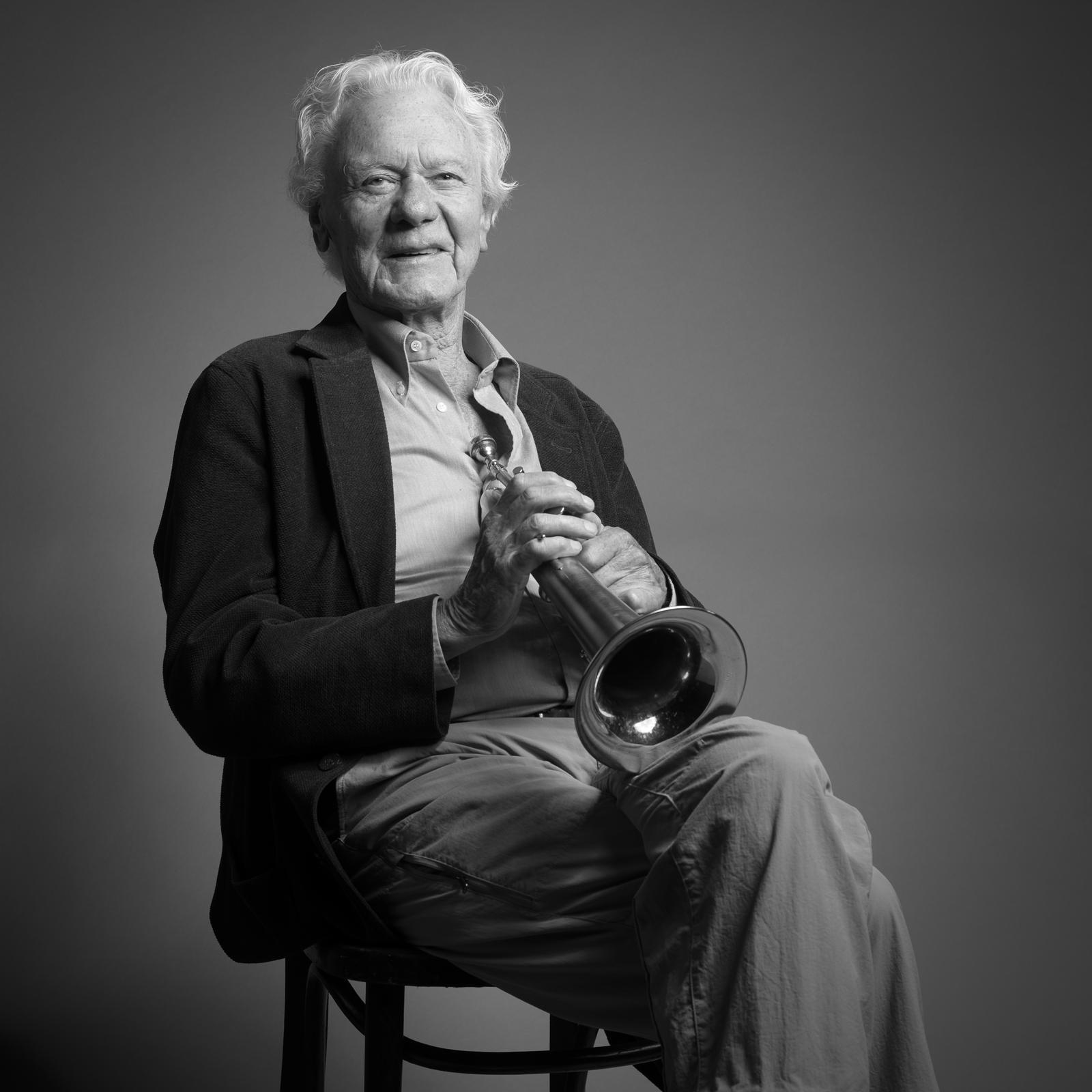 Foto van een man op stoel met trompet