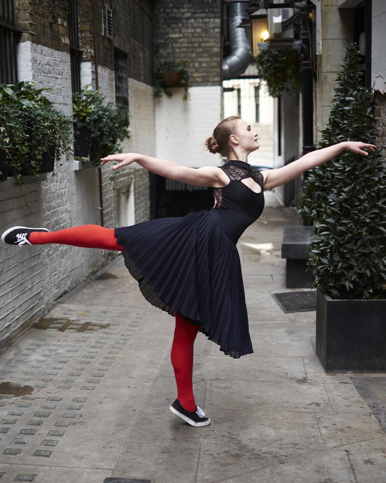 Foto van een ballerina op straat in pose met rode maillot