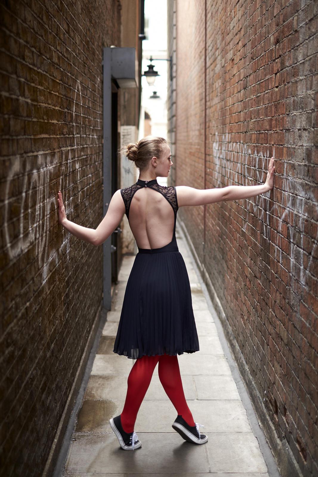 Foto van een ballerina in een steeg met jurk met blote rug