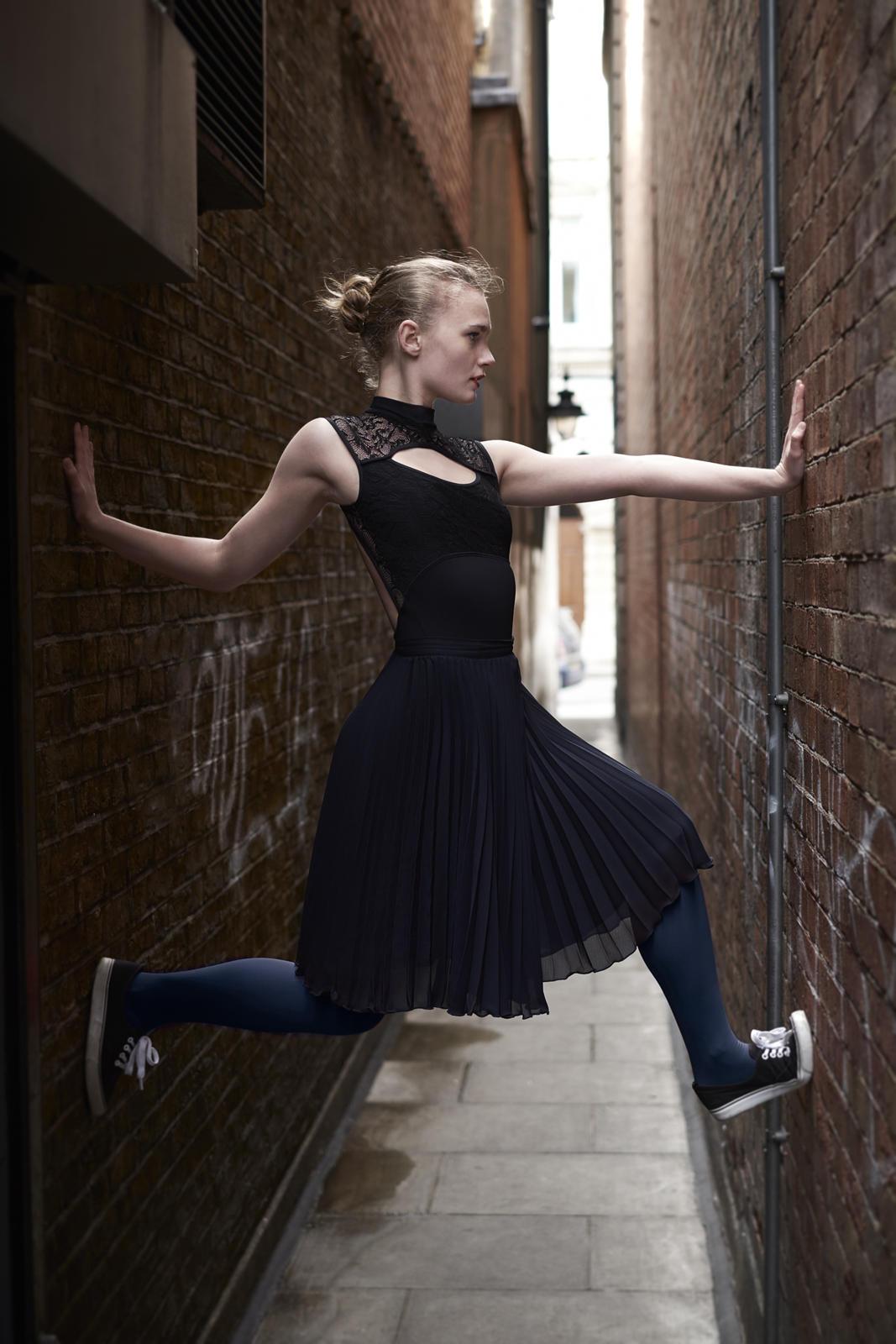 Foto van een ballerina in een steeg met zwarte jurk