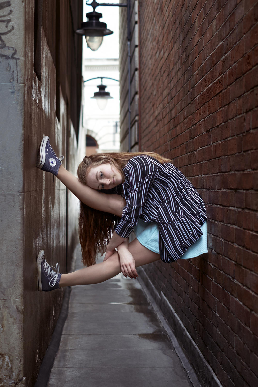 Foto van een ballerina in een steeg die klem zit tussen twee muren