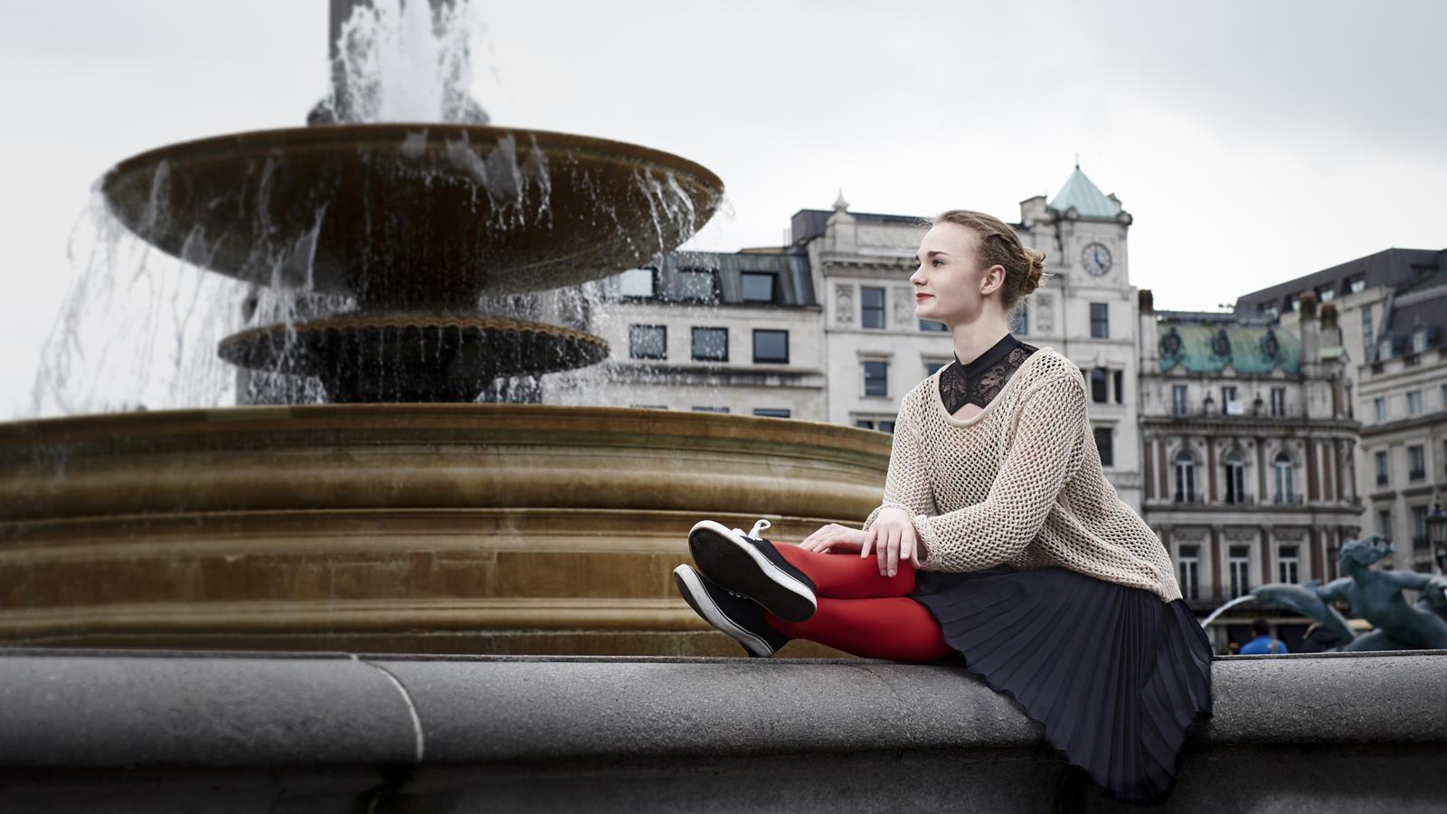 Foto van een ballerina zittend bij een fontein