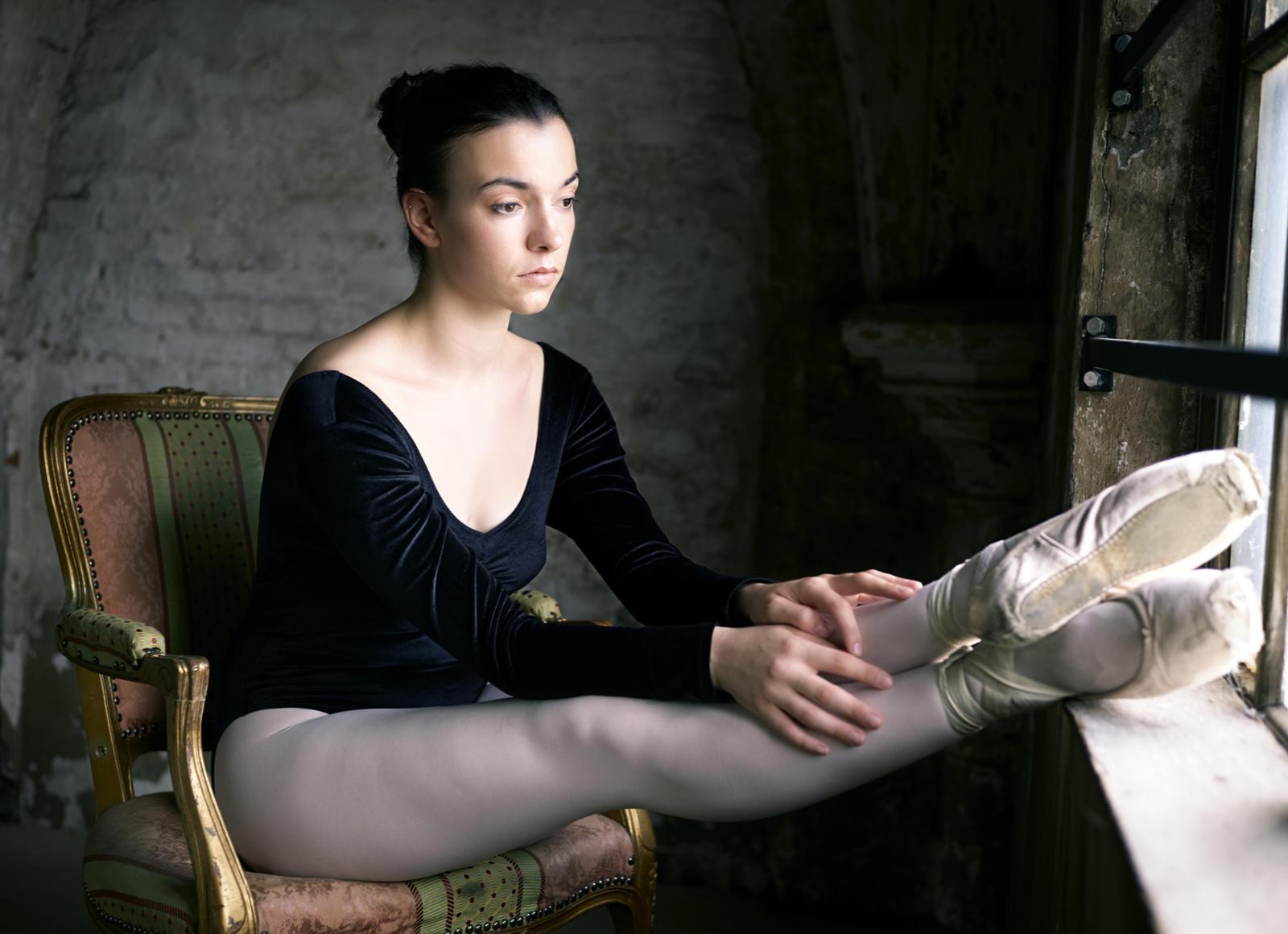 Foto van een ballerina op een stoel bij een raam met benen op vensterbank