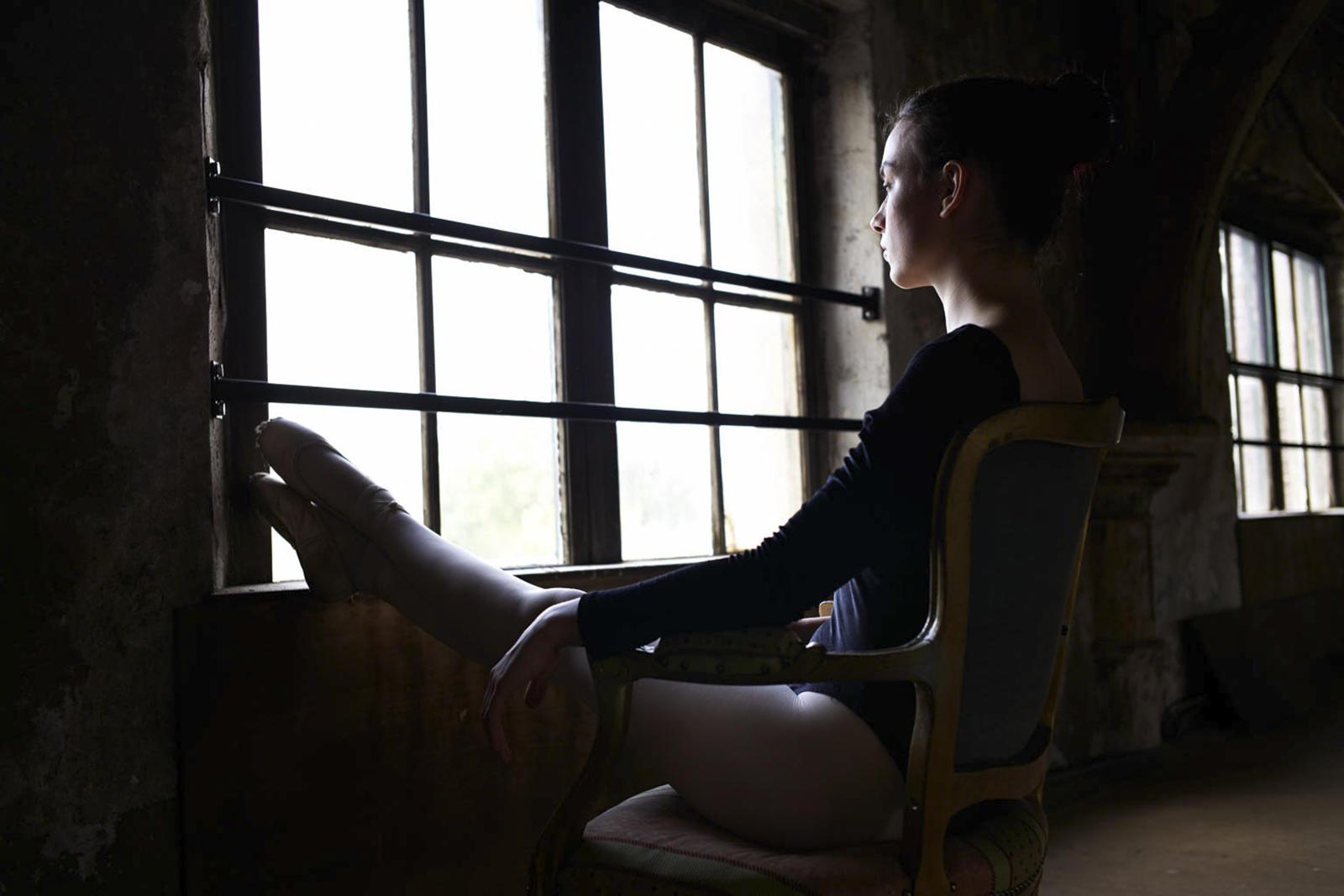 Foto van een ballerina op een stoel bij grote ramen