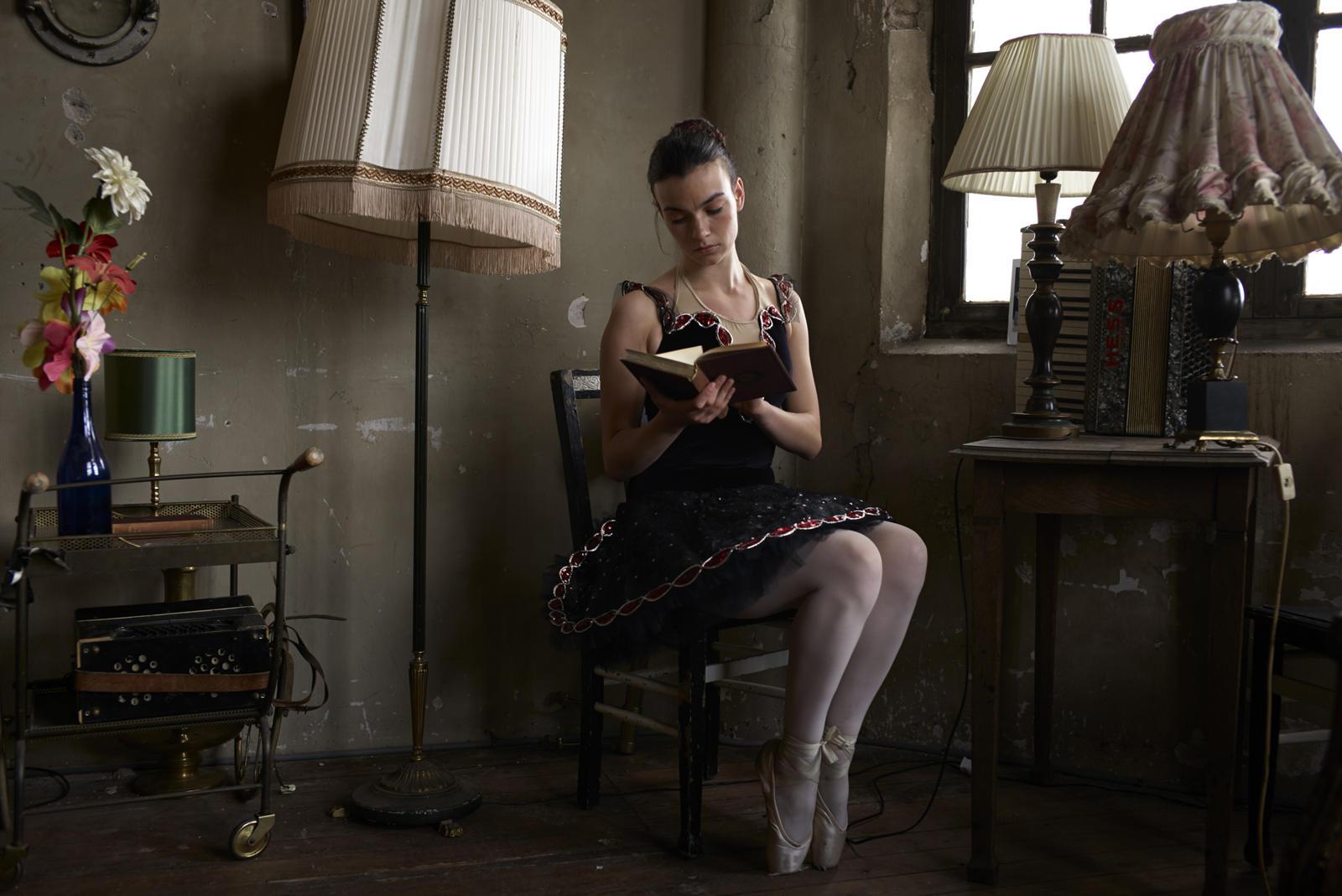 Foto van een ballerina op een stoel die een boek leest in een ouderwets interieur