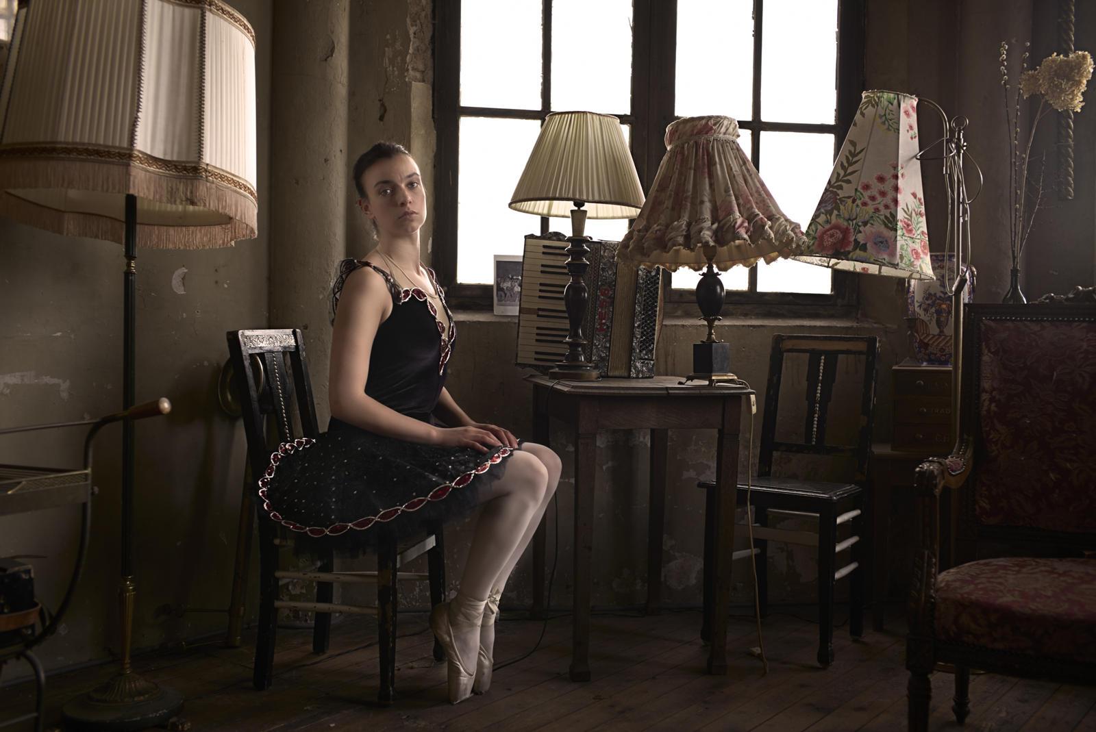 Foto van een ballerina op een stoel in een ouderwets interieur en veel lampenkappen