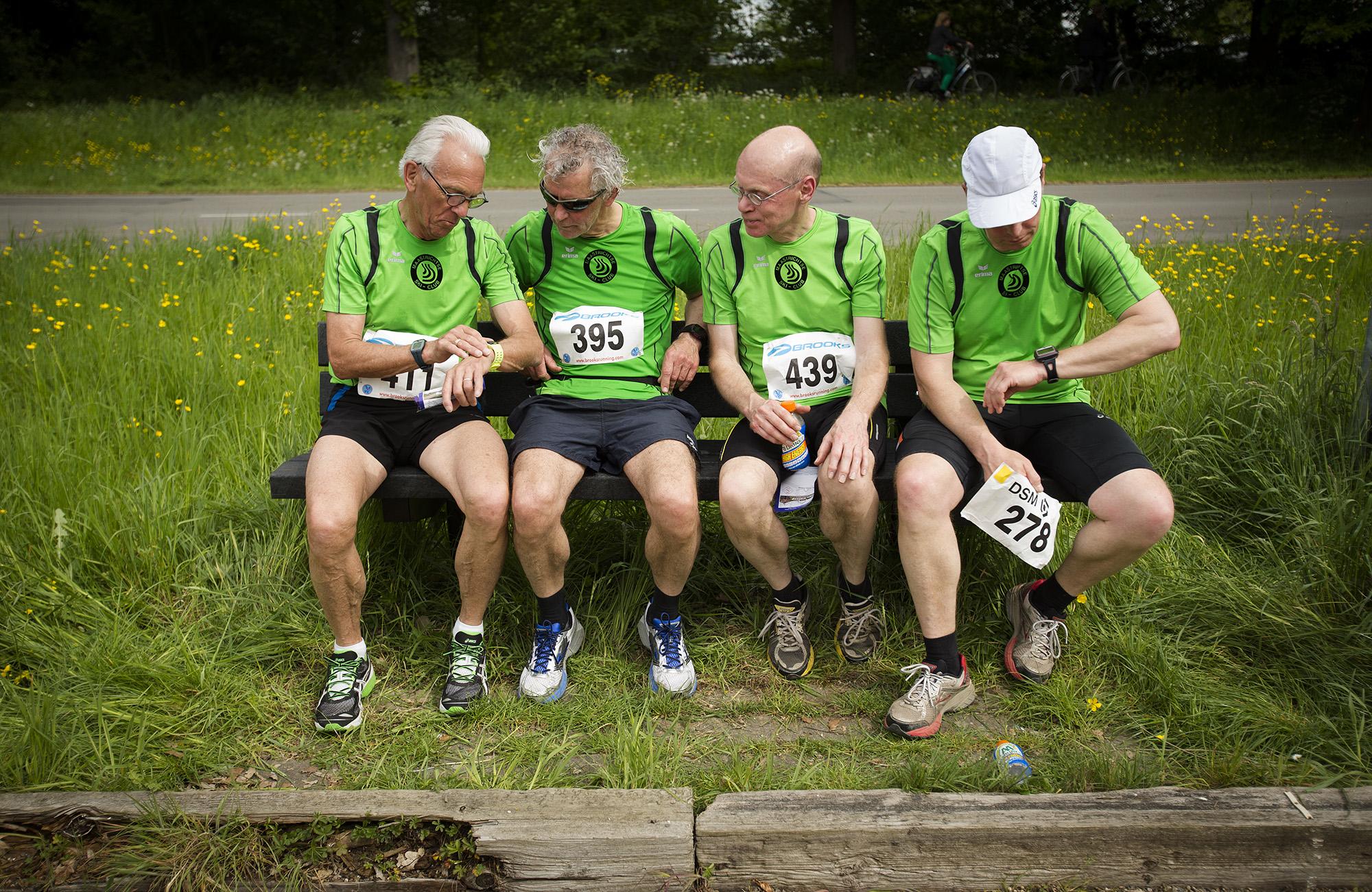 Foto van vier mannen op een bankje in marathon kleding groen