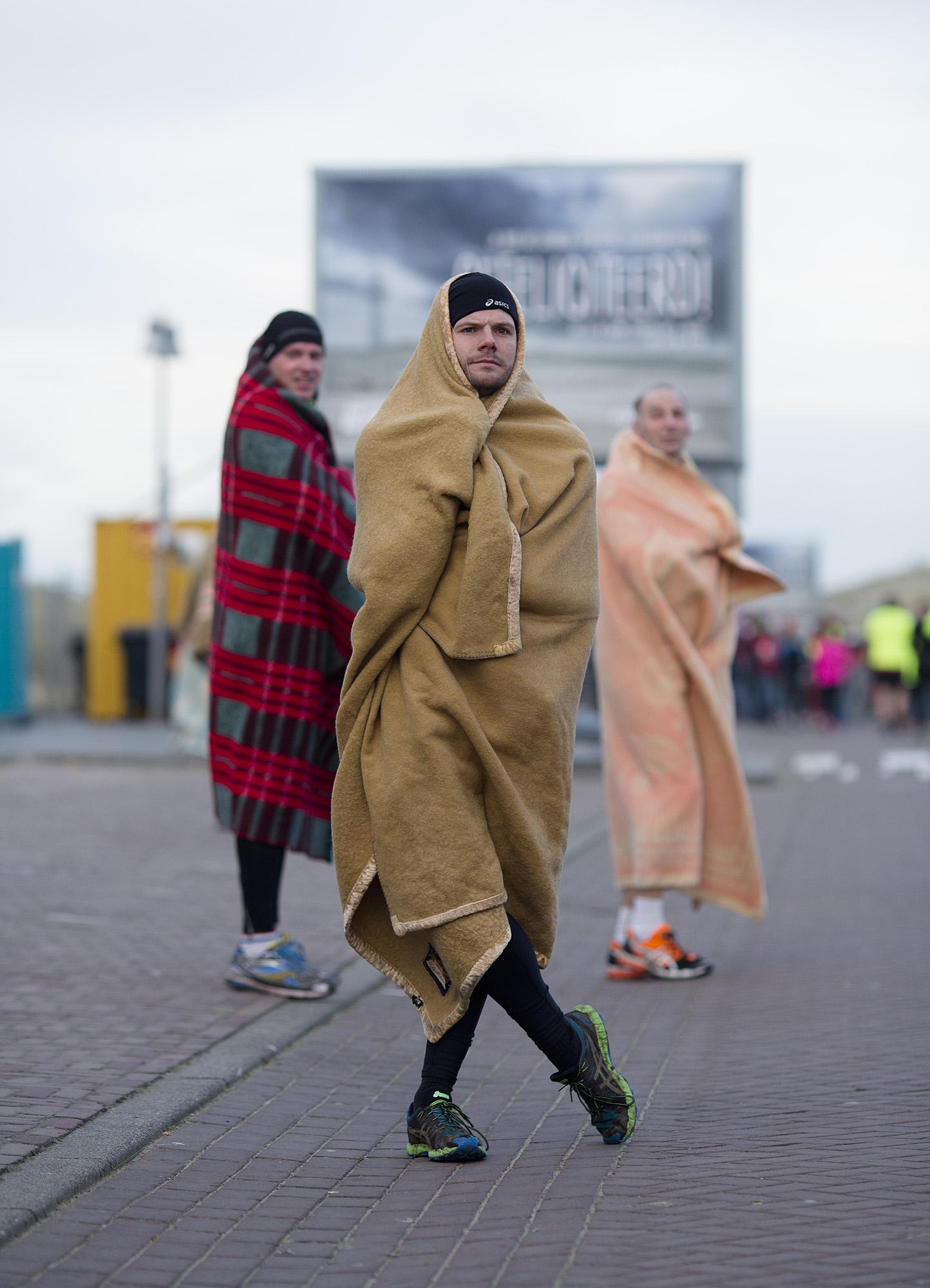 Foto van drie mensen met een deken om zich heen na marathon