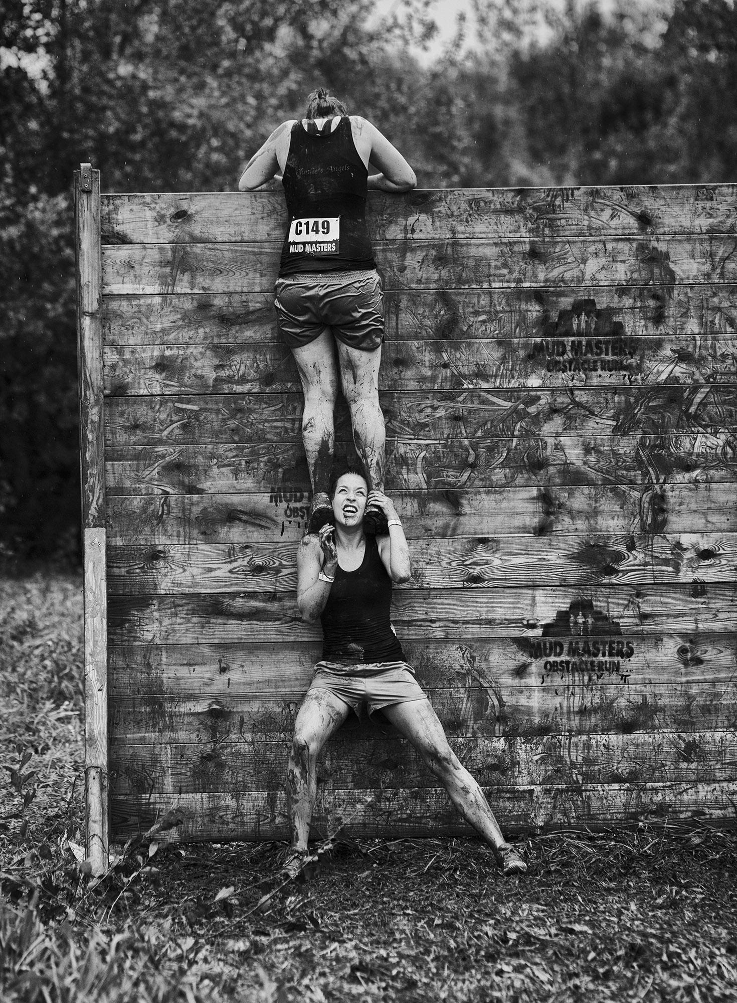 Foto van deelnemer van mudmasters die op schouder van andere deelnemer over houten schutting klimt