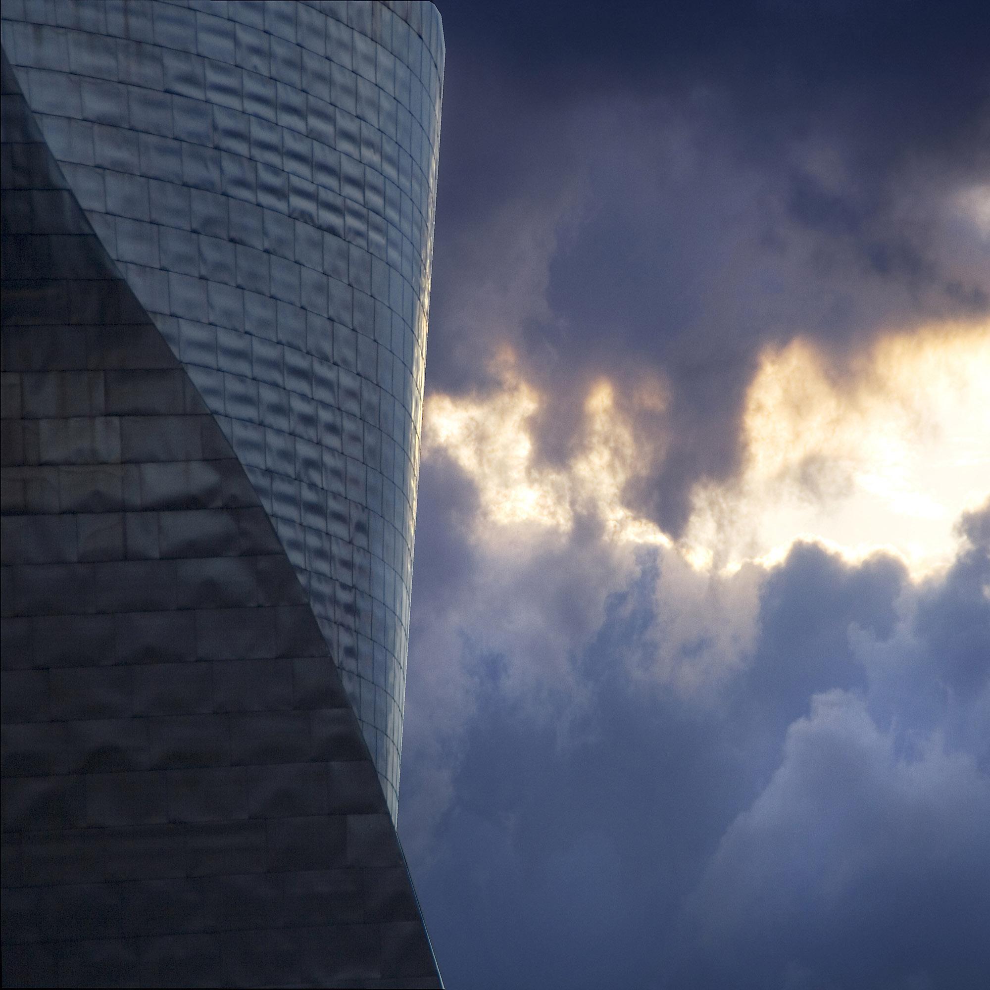 Foto van een deel van een gedraaid gebouw met lucht waar zon door wolken schijnt