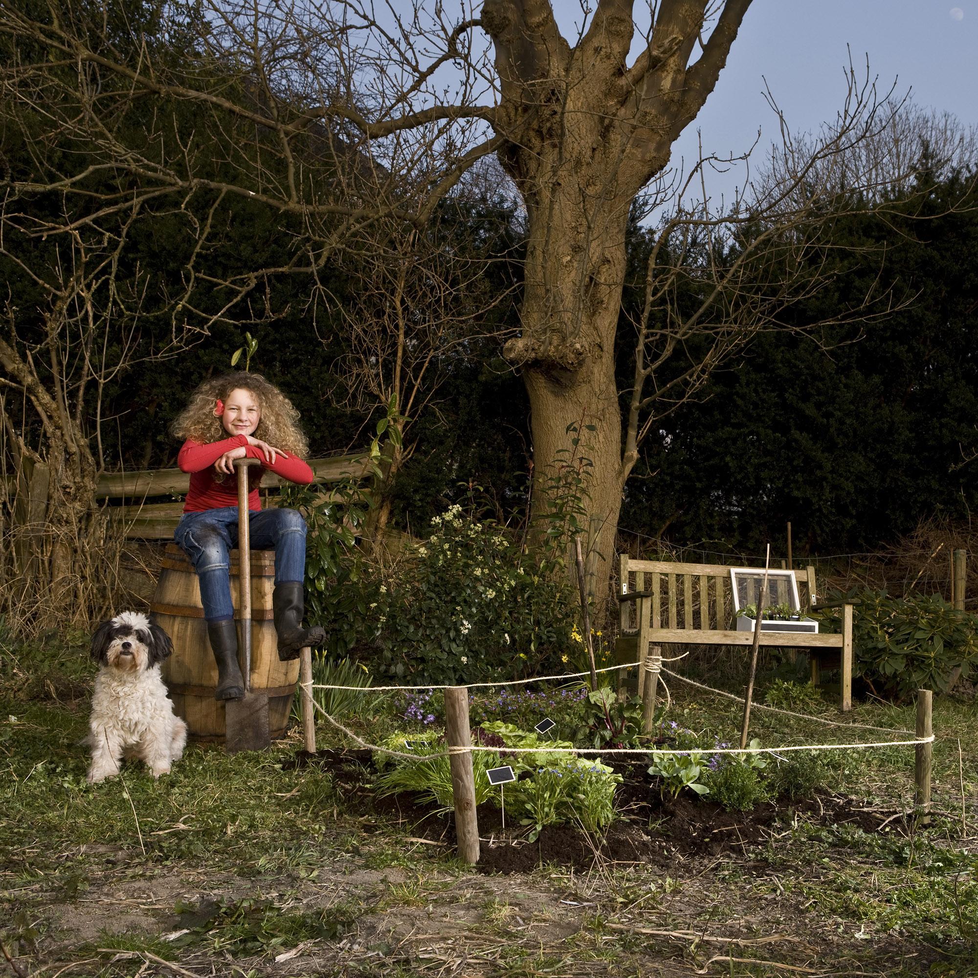 Foto van een meisje in de tuin met hond