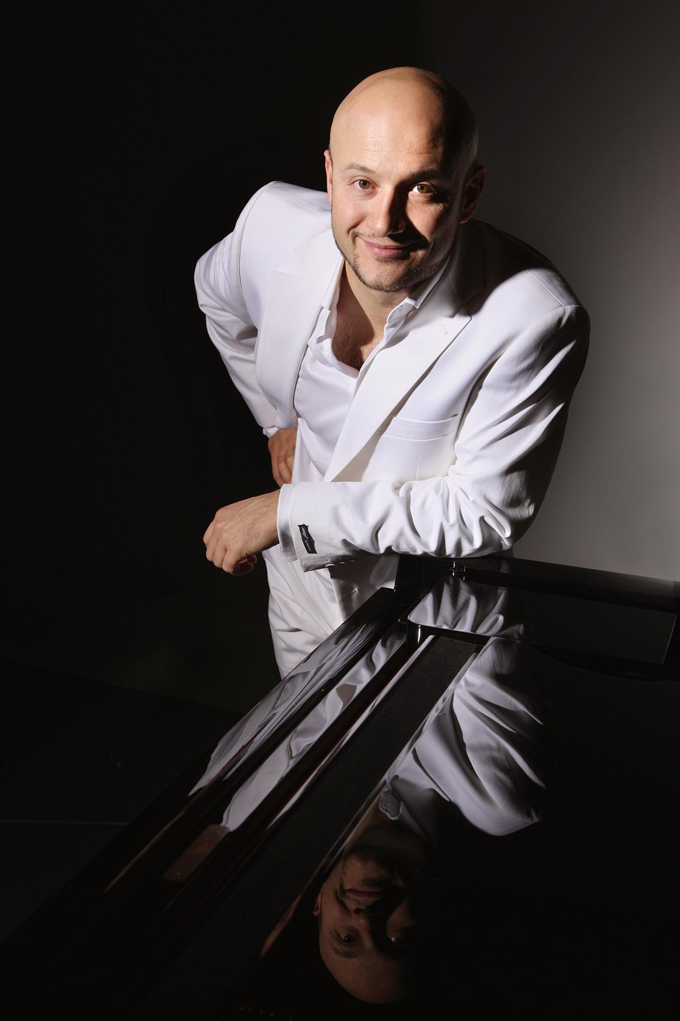 Foto van een man in pak die tegen piano leunt