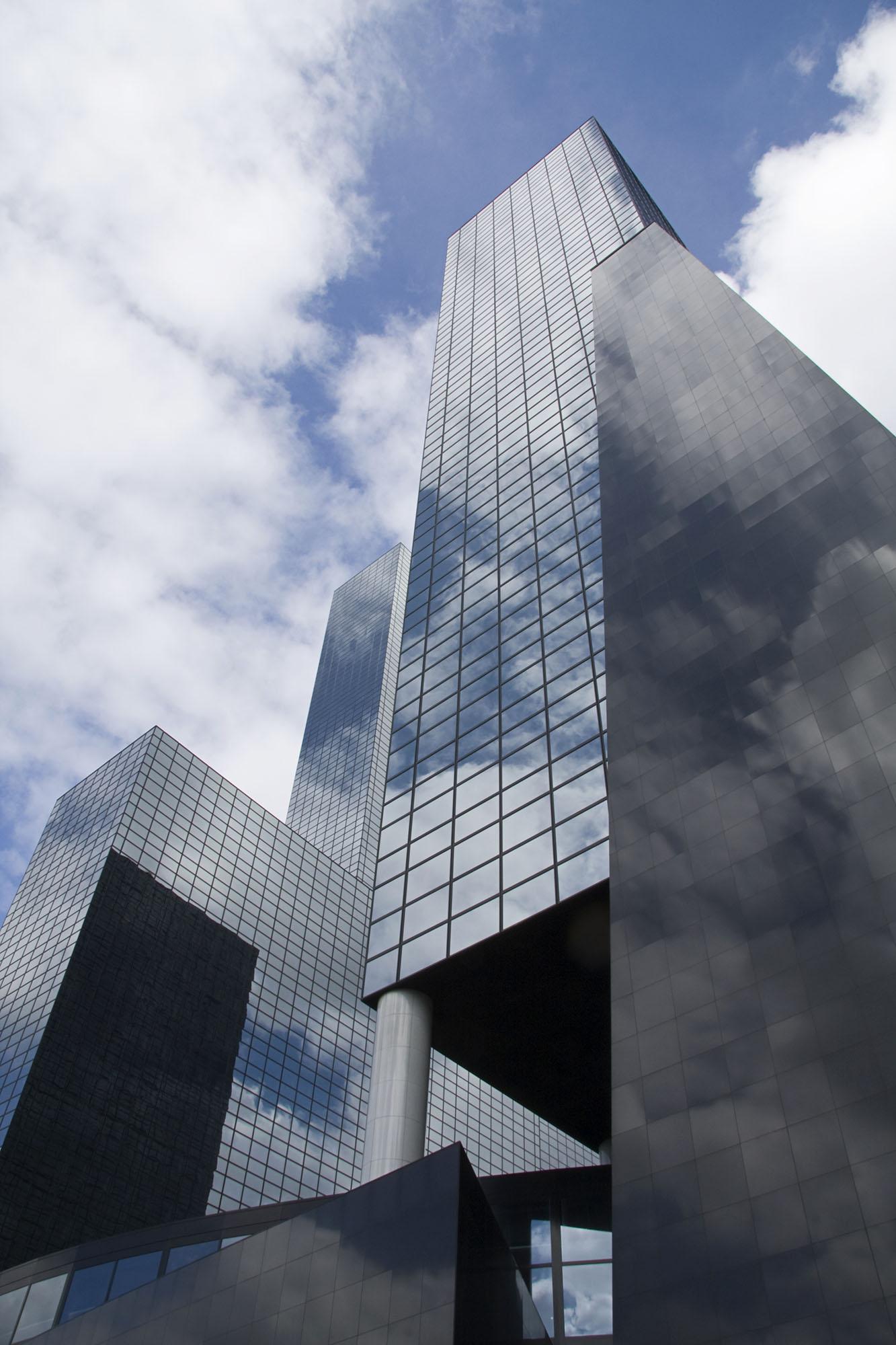 Foto van een gedeelte van een gebouw waarbij de wolken in de spiegel van de gevel herhalen