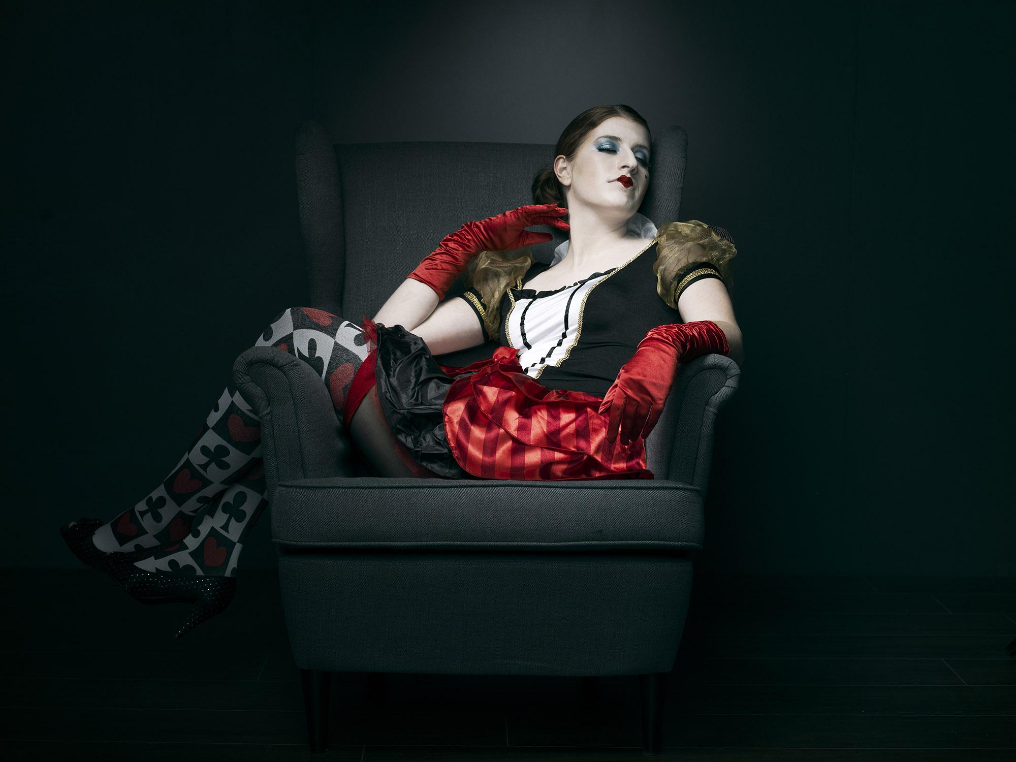 Foto van een verklede vrouw uit sprookje op een stoel met benen naar een kant