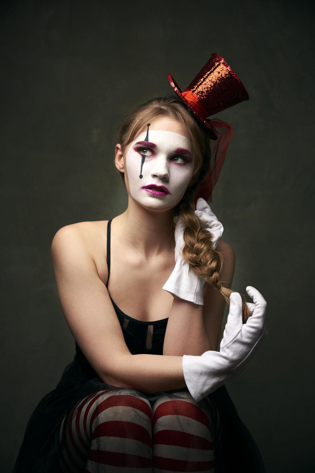 Foto van een geschminkte vrouw met scheef hoedje