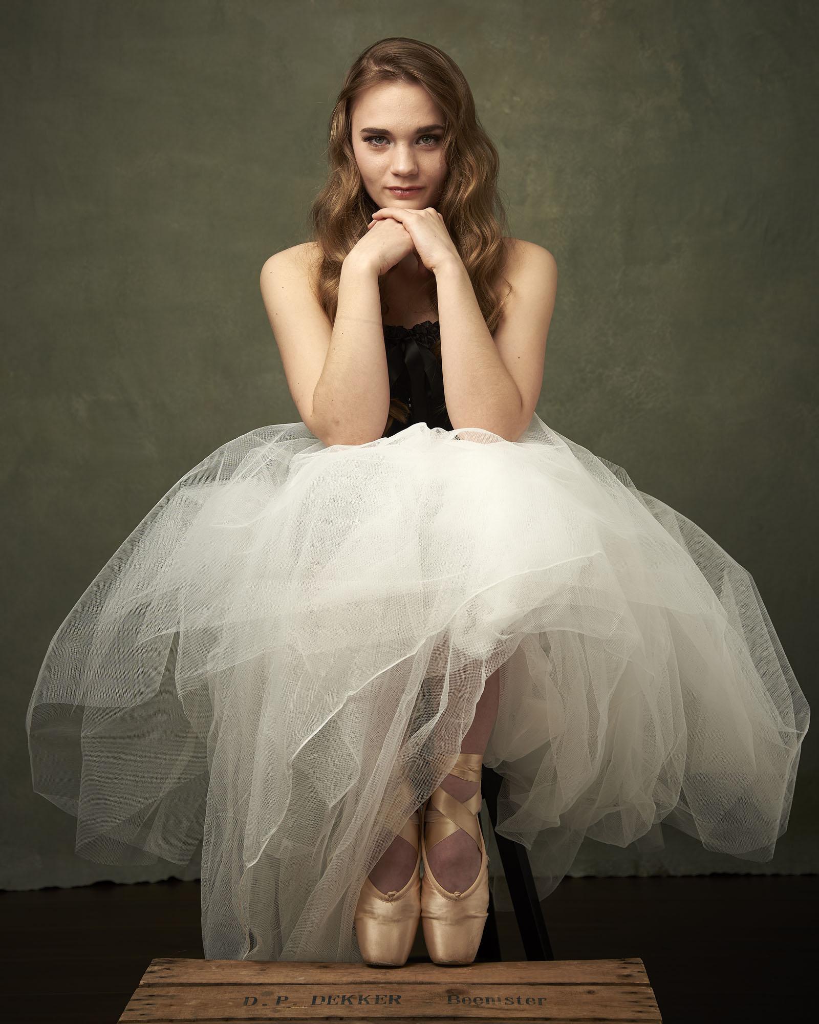 Foto van een vrouw zittend met grote tule rok en balletschoenen