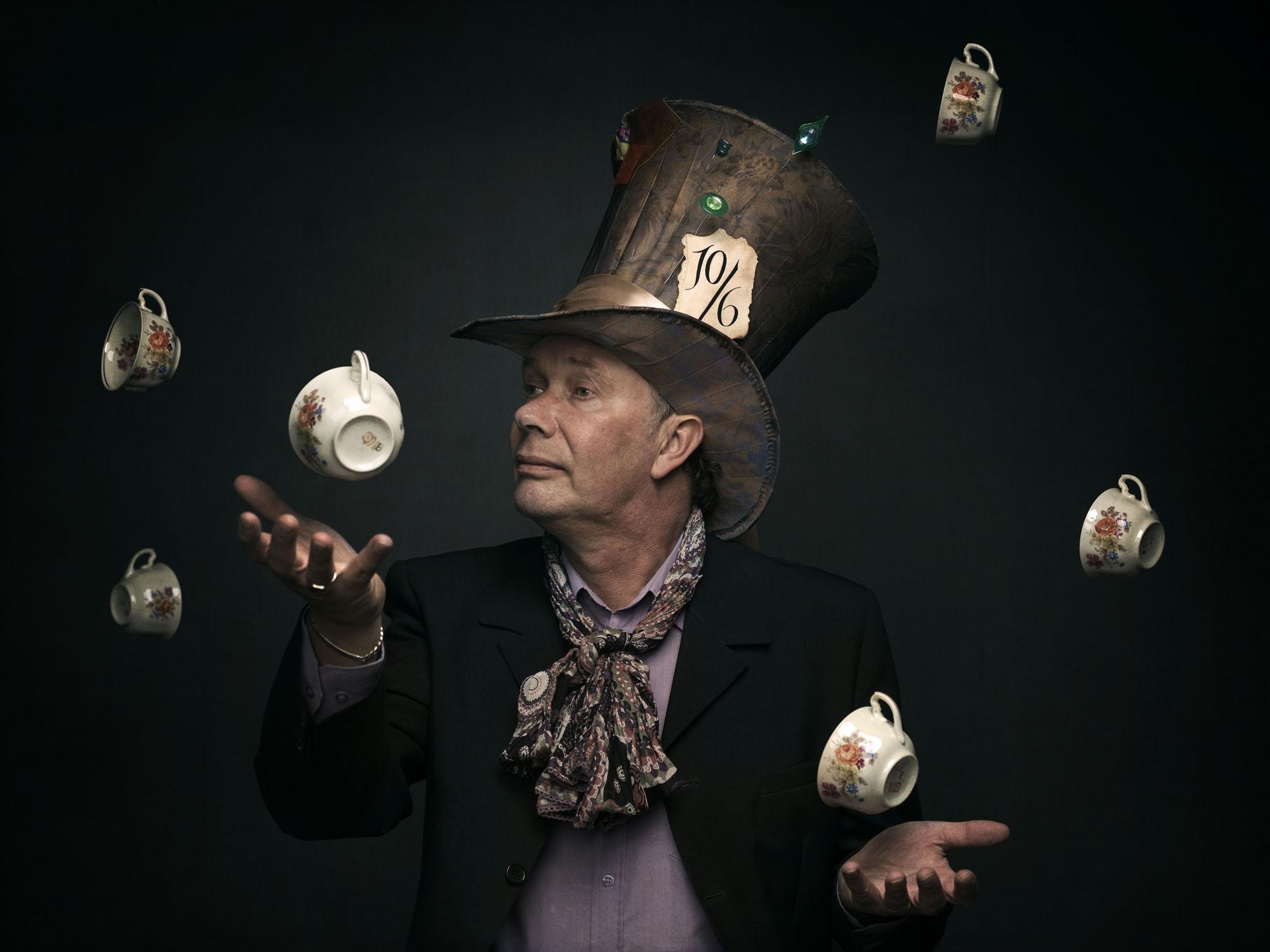 Foto van een man met hoge hoed en theekopjes om zijn hoofd