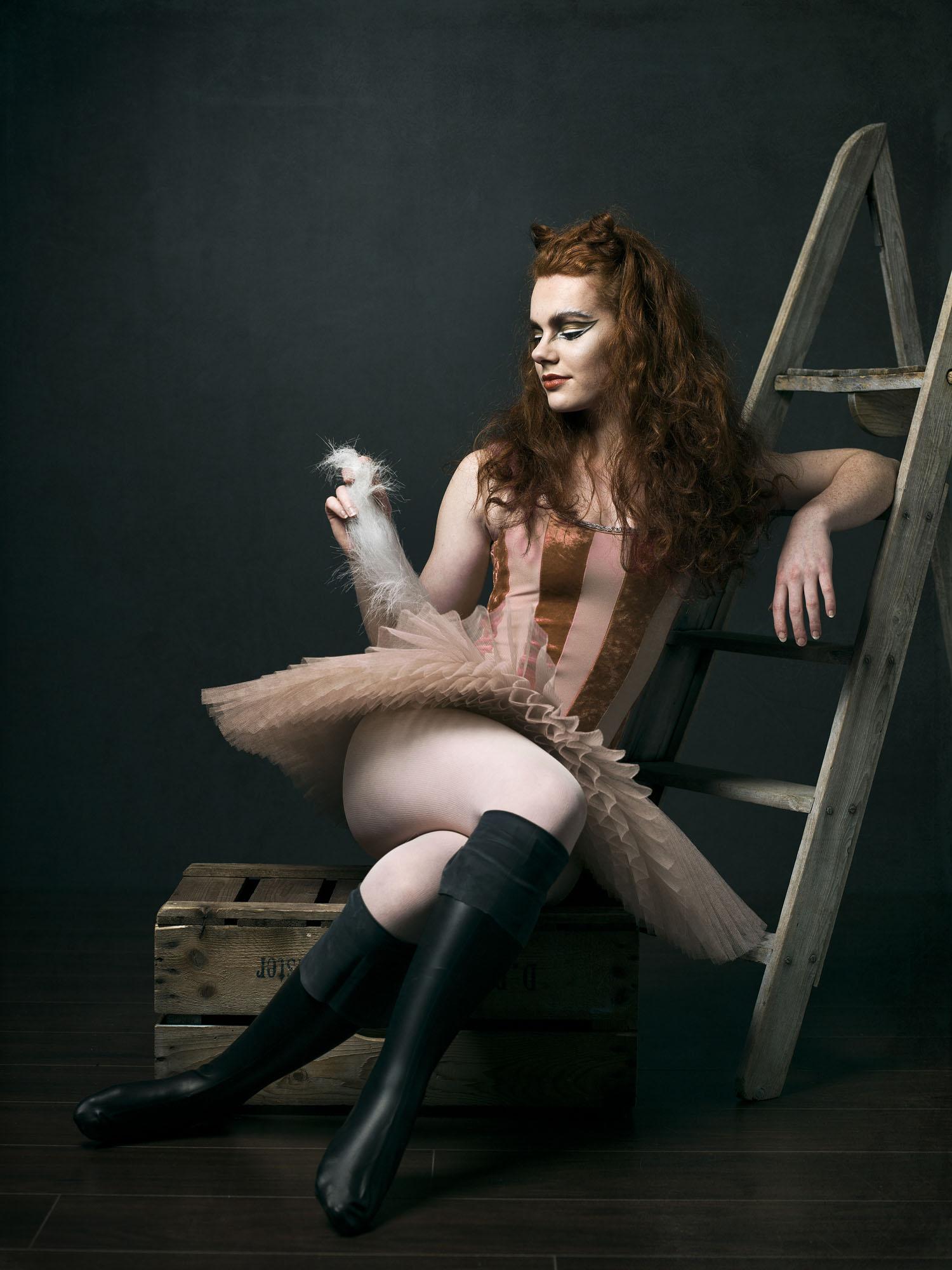 Foto van een vrouw verkleed als gelaarsde kat zittend tegen een trap