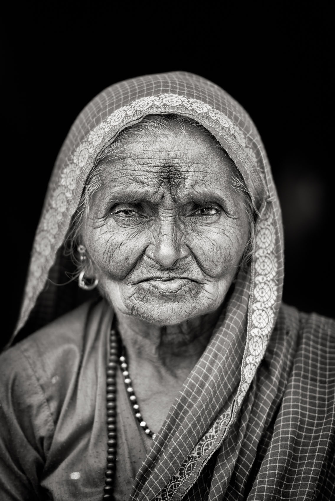 Foto van een vrouw met doek op hoofd en geverfde plek boven neus