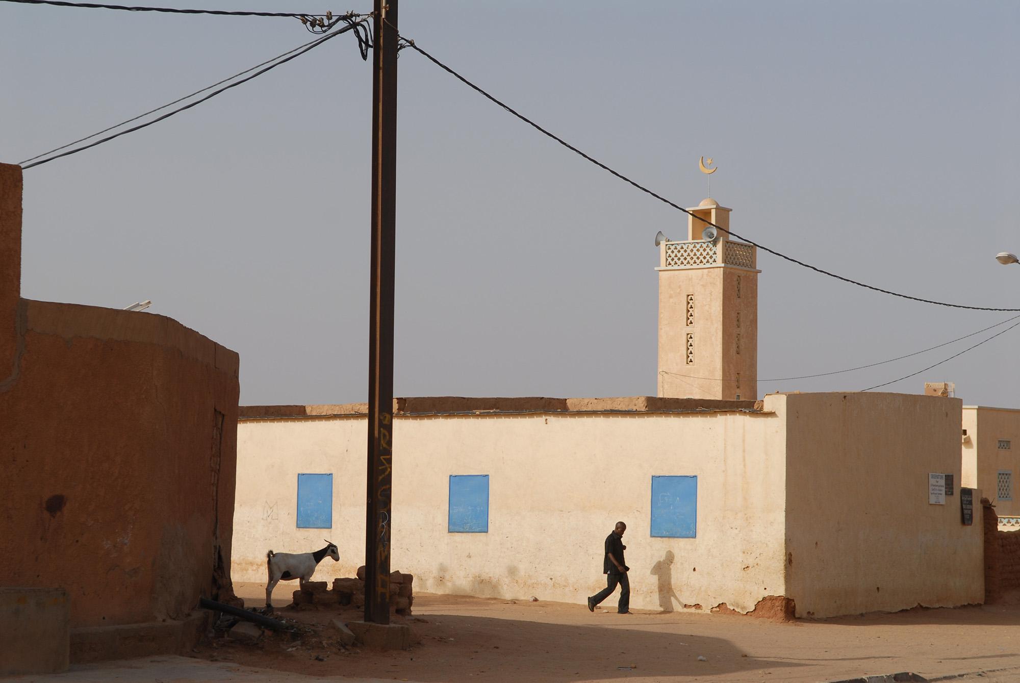 Foto van een man en een geit bij gebouwen in de stad Agadez