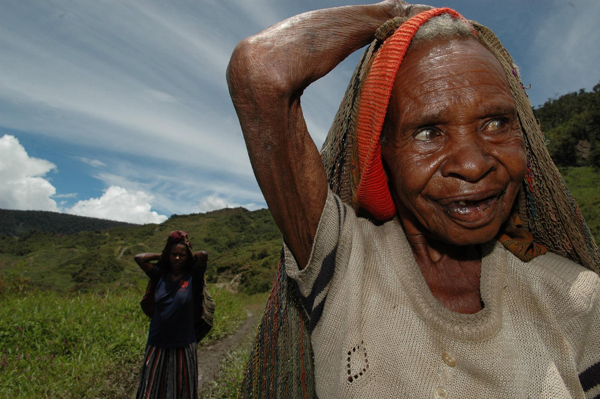 Vrouw met tas op hoofd in landschap
