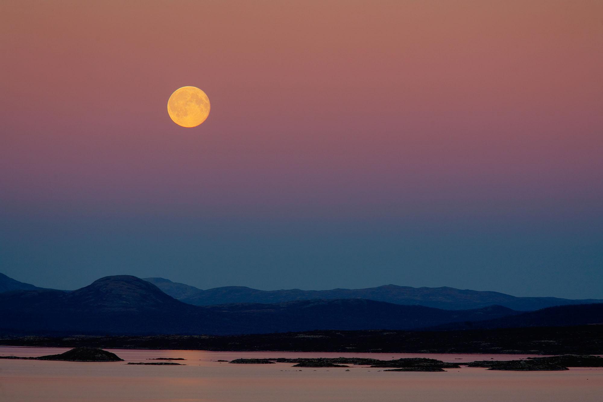 Foto van landschap met bergen en water en maan