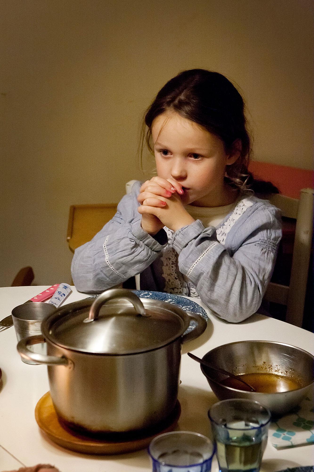 Meisje aan tafel aan het bidden
